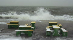 Zone of rest on the embankment during a snowfall and storm tide floods the water Stock Footage