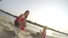 Mom with baby girl one year old playing in the sand on the beach, slow motion - stock footage