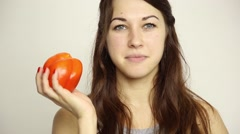 Beautiful young woman eating an vegetables. holding a red pepper. healthy food - Stock Footage
