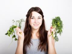 Beautiful young woman eating an vegetables. holding dill and parsley. healthy Stock Photos
