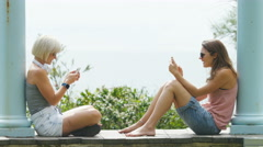 Two young woman sit opposite each other concentrating on their phones Stock Footage