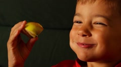Boy eating sour apple and frowns Stock Footage