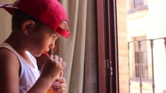 Boy in cap drinking juice through a straw Stock Footage