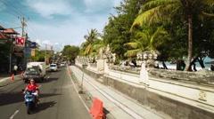 Camera flies backwards above Kuta beach road (jl. Pantai Kuta) Stock Footage