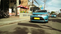 Tracking shot of blue bird taxi driving through Seminyak/Kuta area - front view Stock Footage