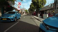 Motorbiker rides between two blue bird taxi cars, Legian street Stock Footage