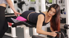 Handsome brunette does exercises on block training apparatus for legs Stock Footage