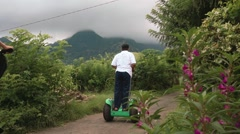 Two women and guide on segway tour in hills in Pemuteran area, cloudy Stock Footage