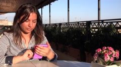 Beautiful young lady with smartphone outdoor sitting at cafe shop pink color 4K Stock Footage