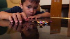 Little boy collect candy from the table and one eats them Stock Footage