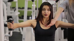 Sportive woman does exercises under guidance of coach in gym - stock footage