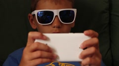Little boy playing game on mobile phone wearing sunglasses Stock Footage