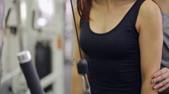 Woman trains her arms with rope in gym under guidance of trainer - stock footage