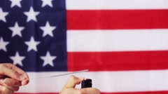 Close up of hand with sparkler over american flag Stock Footage