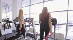 Woman and her trainer walk together on treadmill in gym Stock Footage