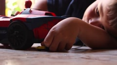 Little boy playing toy cars on the floor Stock Footage