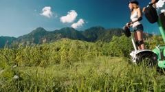 Two people on segway side by side in Pemuteran hills and mountains, low angle Stock Footage