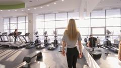 Elegant blonde woman gracefully walks through sport club Stock Footage