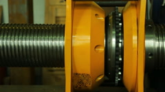 Worker twists metal part with thread in yellow press, by hand Stock Footage