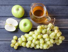 Apple and grapes, a pitcher of juice, still life - stock photo
