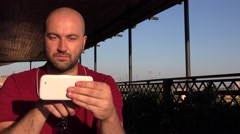 Angry business man with red t-shirt working on mobile phone at cafe shop outdoor - stock footage
