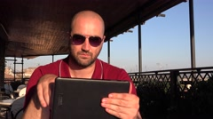 Business man in holiday time relaxing on digital tablet wear sunglasses terrace - stock footage