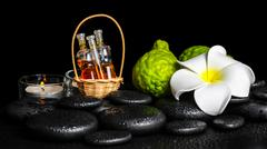 Aromatic spa setting of bergamot fruits, candles, plumeria flower and bottles Stock Photos