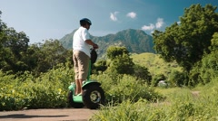 Three people on segway in Pemuteran hills in front of mountains Stock Footage