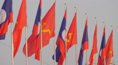 Lao national and communist flags in light wind,Vientiane,Laos - stock footage
