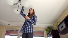 Woman climb up and change light bulb to eco Stock Footage