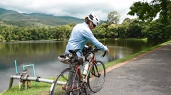 Side rear angle of cyclist checking bike Stock Footage