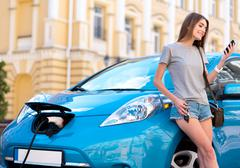 Woman looking at phone near hybrid car Stock Photos
