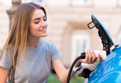 Woman charging battery of eco car - stock photo