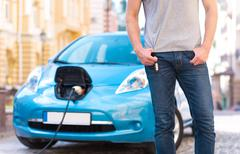 Man standing in front of electric car Stock Photos