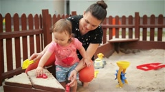 Mother and baby daughter playing in the sandbox and making shapes, beautiful - stock footage