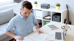 Handsome man doing paperwork at home office Stock Footage