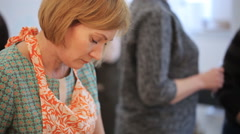Blonde middle-aged woman lowers her head and crafts - stock footage