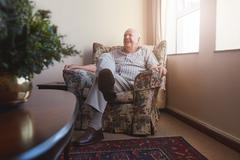 Elderly man sitting on arm chair at old age home Stock Photos