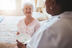 Senior woman on bed with nurse giving medication Stock Photos