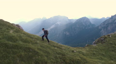Aerial - Tracking shot of a hiker walking uphill on the edge of a cliff Stock Footage
