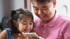 Little Asian girl playing game on mobile phone with her father Stock Footage