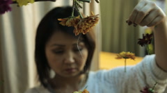 Chinese woman accurately hangs out floral decoration on wall Stock Footage