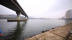 Two fishermen catch fish under the bridge on Hong Kong bund. Stock Footage