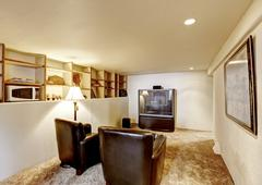 Antique family room with old TV and two leather armchairs. Also some shelves  Stock Photos