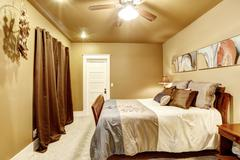 Nice bedroom with mocha interior paint and beige carpet. Also large wooden be Stock Photos