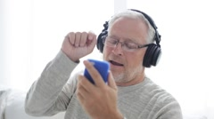 Happy senior man with smartphone and headphones 16 Stock Footage