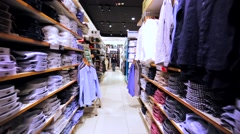 Walking along the shelves with clothes in Uniqlo store in Hong Kong mall. Stock Footage