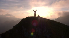 Aerial - Silhouette of a man standing on top of the mountain with arms raised - stock footage
