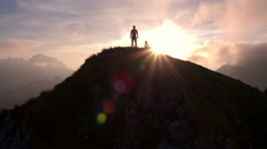 Aerial - Moving above silhouette of a man standing on top of the mountain Stock Footage