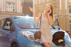 Woman talking on smartphone and charge car Stock Photos